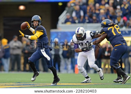 MORGANTOWN, WV - November 1: WVU quarterback Clint Trickett (#9) prepares t throw as he rolls out away from pressure during the Big 12 football game November 1, 2014 in Morgantown, WV.  - stock photo