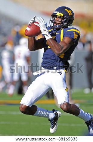 MORGANTOWN, WV - NOVEMBER 5: WVU wide receiver Ivan McCartney catches a pass as he leaps in the air prior to the football game against Louisville November 5, 2011 in Morgantown, WV. - stock photo