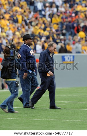 MORGANTOWN, WV - OCTOBER 23: Former West Virginia University head football coach Don Nehlen (right) walks off the field after the coin flip on October 23, 2010 in Morgantown, West Virginia. - stock photo