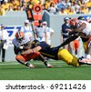 MORGANTOWN, WV - OCTOBER 23: West Virginia University linebacker Chris Neild (blue jersey) tackles Syracuse running back Antown Bailey (No. 29) for a loss on October 23, 2010 in Morgantown, WV. - stock photo