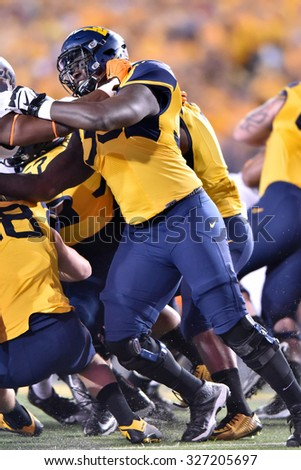 MORGANTOWN, WV - OCTOBER 10:  WVU offensive lineman Yodny Cajuste (55) blocks on a running play during the Big 12 football game October 10, 2015 in Morgantown, WV.  - stock photo