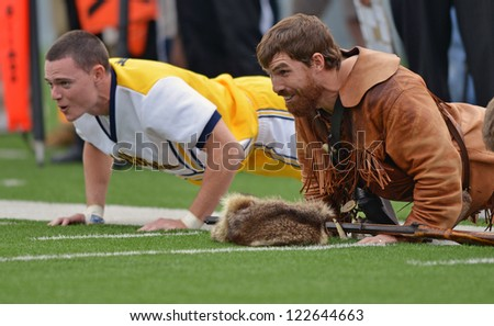 MORGANTOWN, WV - SEPTEMBER 29: The WVU mascot joins cheerleaders in push ups following a WVU score in a Big 12 conference football game September 29, 2012 in Morgantown, WV. - stock photo