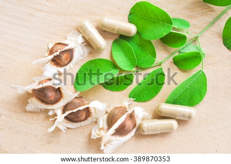 Moringa seeds with leaves and powder in capsule in natural light on wood background, selected focus area. Alternative Medicine - stock photo