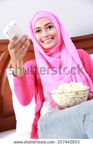 morning activity of young muslim woman watching television while eating popcorn - stock photo