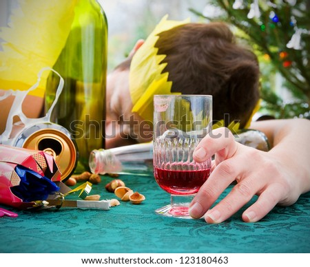 morning after christmas day, woman asleep on table with alcohol at christmas landscape - stock photo