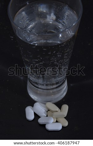 Morning After the Night Before. A still life image of sparkling mineral water and vitamin tablets with a dark background that implies a long night out on the town with a dehydration issue after it.  - stock photo