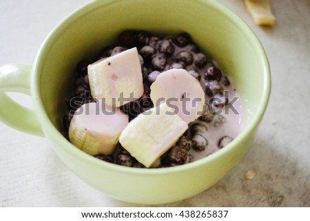 morning breakfast bananas yogurt cereals in bowl on old rustic table - stock photo