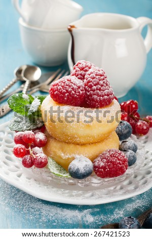 Morning breakfast with mini donuts and berries on plate under powdered sugar on blue wooden background.  Tasty donuts closeup. Doughnut. Selective focus.  - stock photo