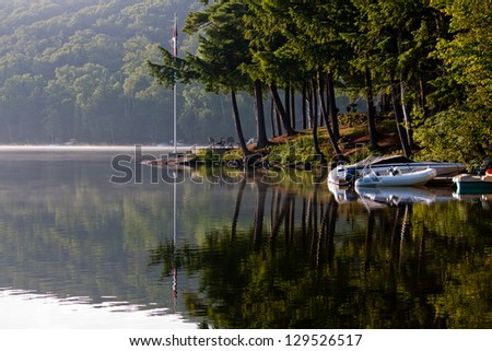 Morning breaks over the glassy still lake, looking out at boats docked and Muskoka pine trees - stock photo