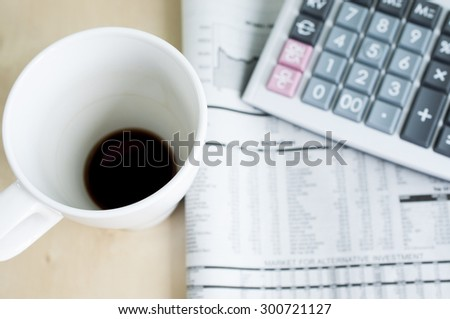 Morning business news with empty cup of coffee and calculator blur backgrounf - stock photo
