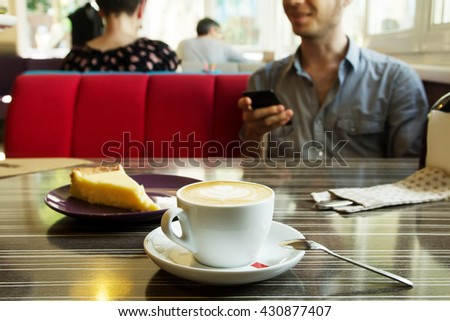 Morning cappuccino coffee and cheesecake. Cheesecake and kitchen appliances on the background. Coffee with art foam. Guy with the phone drinks cofee. - stock photo