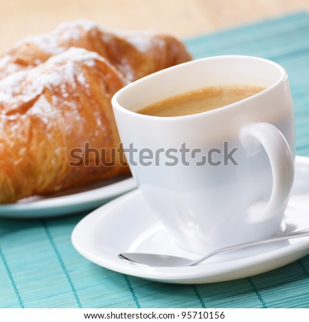 Morning cappuccino coffee with croissant on the wooden table - stock photo