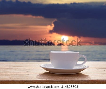 Morning coffee cup with seascape sunrise background - stock photo