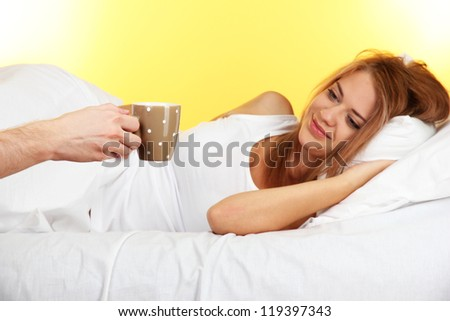 morning coffee in bed for young  woman on yellow background - stock photo