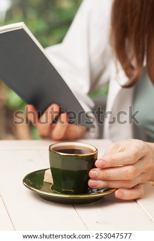 Morning coffee. Young woman drinks coffee while reading a book - stock photo