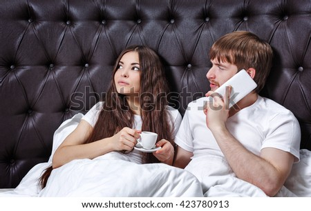 Morning couples. Wife drinks coffee. Man talking on cell phone. Conversation. Morning at the hotel. Business people. - stock photo