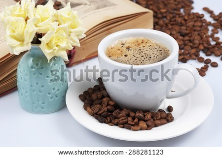 morning cup of coffee with cream and book - stock photo