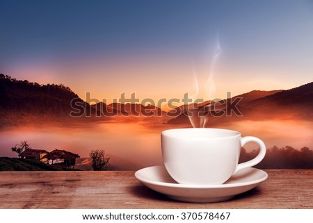 Morning cup of coffee with tea tree in mountain background at sunrise - stock photo