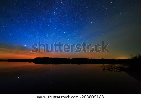 Morning dawn on a starry background sky reflected in the water of the lake. - stock photo