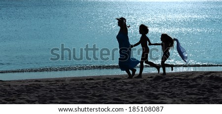 Morning exercise silhouettes - woman and kids running on the beach at sunrise - stock photo