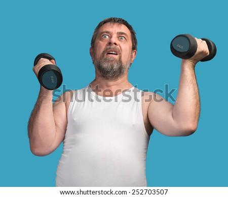 Morning exercises. Elderly man exercising with dumbbells  - stock photo