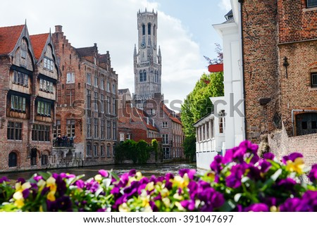 Morning in the old town with a river. Beautiful flowers on foreground. Bruges. - stock photo
