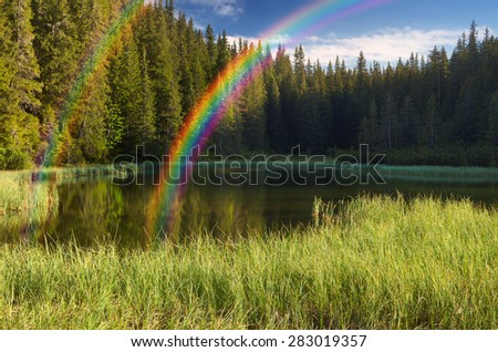 Morning landscape with forest lake and rainbow - stock photo