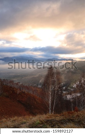 Morning landscape with trees in foreground and clouds with fog in background. Late Winter scene.  - stock photo