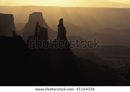 Morning light filters in on the Washer Lady as seen from Mesa Arch at Sunrise Canyonlands National Park Utah - stock photo