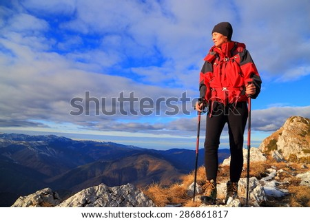 Morning light illuminates a backpacker woman on the mountain - stock photo
