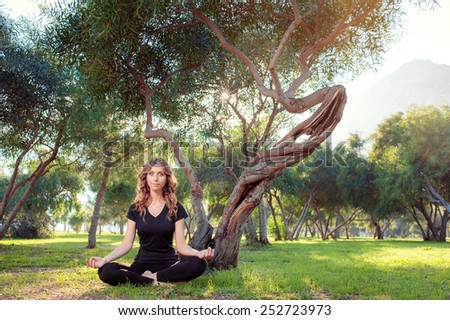 Morning meditation. Young woman in lotus pose in the park sitting on green grass. - stock photo