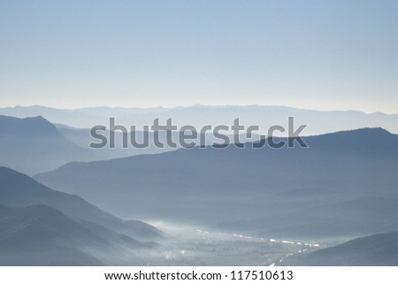 Morning mist at a valley on the way to Lijiang from Dali in Yunnan province, China, with layers of mountain at the background. - stock photo