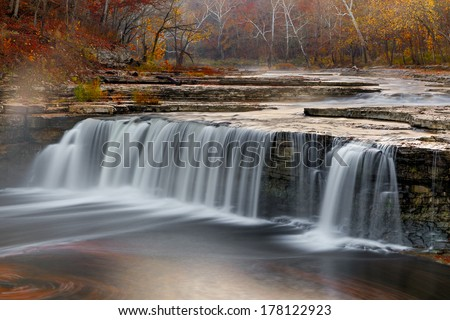 Morning mist rises over Indiana's Lower Cataract Falls surrounded by a vibrant autumn landscape. LIeber State Recreation Area (Cataract Lake State Park), Indiana, USA.  - stock photo