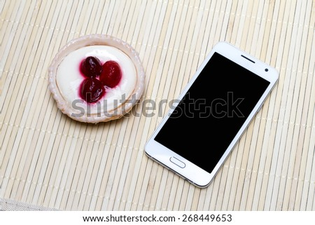 Morning Mood, where on a light table is a phone with Cake - stock photo