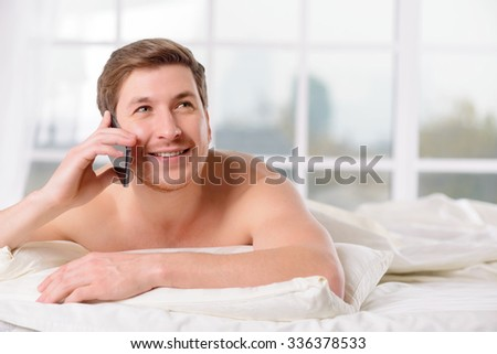 Morning phone call. Young handsome man rests in bed while talking lazily on the phone. - stock photo