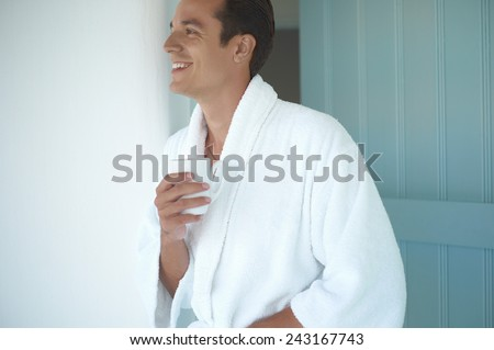 Morning portrait of handsome young man with cup of coffee - stock photo