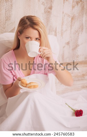 Morning relax. Top view portrait of young woman drinking coffee with croissant while lying in bed with red rose on the blanket - stock photo
