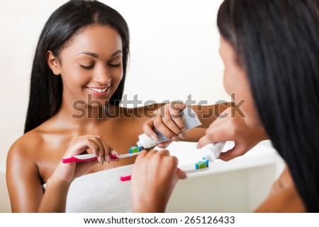 Morning routine. Beautiful young African woman squeezing toothpaste on a brush and smiling while standing against a mirror in bathroom - stock photo