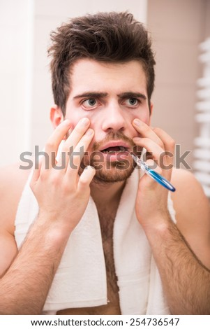 Morning routine of washing the teeth. Tired young man is brushing teeth with toothbrush. - stock photo