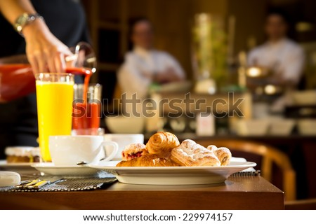 Morning scene of pouring fresh juices at hotel breakfast table - stock photo