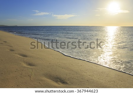 Morning sun shines on the calm ocean - stock photo