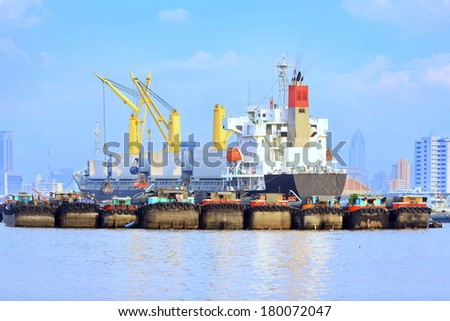 Morning sunlight crane loading product to Cargo ships entering one of the busiest ports in the world,  - stock photo