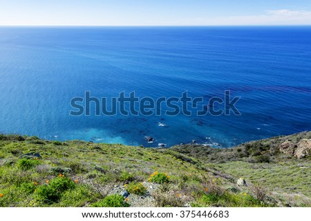 Morning sunrise, beautiful shimmering blue sea & sky, aquamarine waters, gentle surf, along steep sheer jagged cliffs, traveling the Big Sur Highway, on the California Central Coast, near Cambria CA. - stock photo