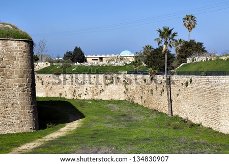 Morning time at the old town of Acco (Acre), Israel. Amongst the green weeds carpet, a path created by thousands of strolls fades into the shadow cast by the immense wall that rises above. - stock photo