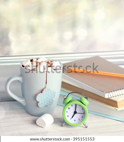 Morning time cocoa mug alarm clock at windowsill.Day start wake up concept.Early breakfast stack of books on wooden background empty space. - stock photo