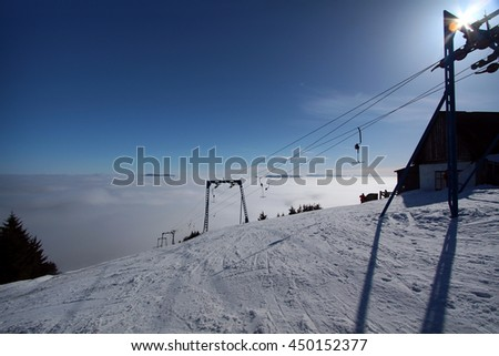 morning tranquil ski resort with clouds in a valley - stock photo