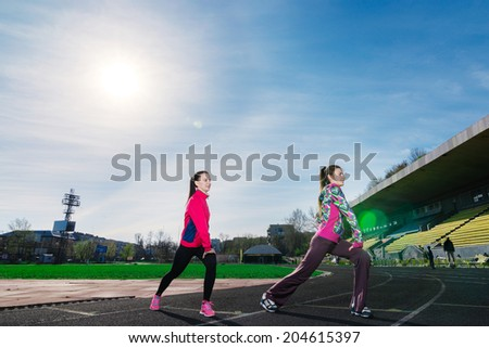 Morning warm-up and stretching exercises! Two attractive young women in sports clothing stretching together and smiling at the stadium outdoor - stock photo
