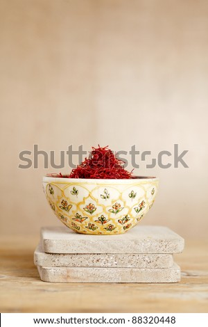 moroccan saffron threads in bowl, on wood, shallow dof - stock photo