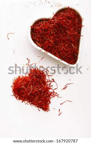 moroccan saffron treads in heart pile, on white wood, shallow dof - stock photo