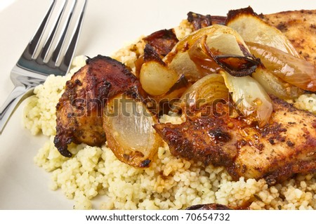 Moroccan Spiced Chicken with couscous and onions isolated on white. - stock photo
